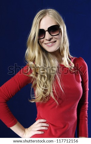Young woman wearing sunglasses against blue background - stock photo