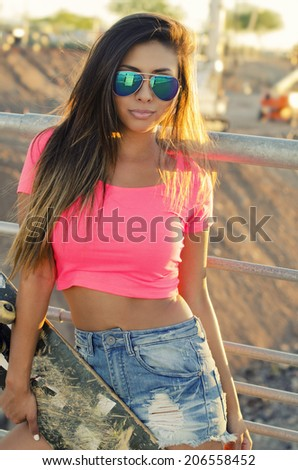 Young woman wearing sunglasses holding skateboard