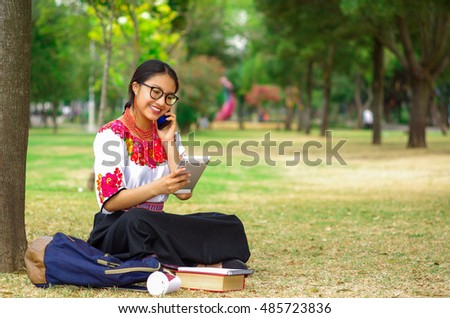 Young woman wearing traditional andean skirt and blouse with matching red necklace, sitting on grass next to tree in park area, relaxing while smiling happily