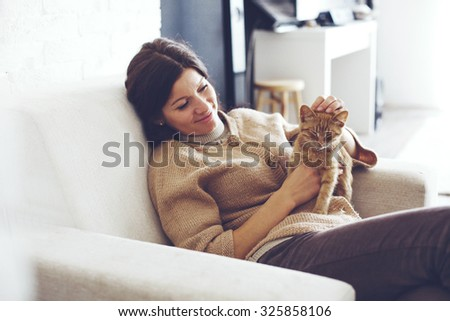 Young woman wearing warm sweater is resting with a cat on the armchair at home one autumn day - stock photo