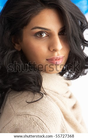 Young Woman Wearing Warm Winter Clothes And Fur Hat In Studio - stock photo