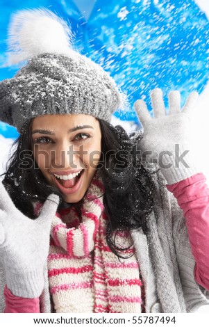 Young Woman Wearing Warm Winter Clothes And Hat Being Hit By Snowball In Studio - stock photo
