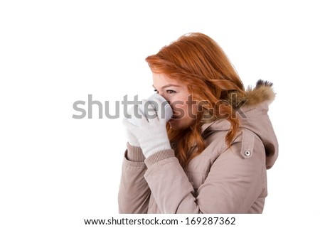 Young woman wearing winter clothes and drinking hot drink from a black cup, isolated on white background. - stock photo