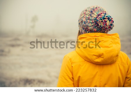 Young Woman wearing winter hat clothing outdoor Travel Lifestyle and melancholy emotions concept foggy nature on background  - stock photo