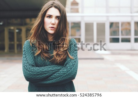 Young woman wearing woolen green sweater walking in the winter city street. Warm soft cozy image. Cold weather