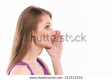 Young woman whispering over white background. profile of beautiful girl whispering message - stock photo