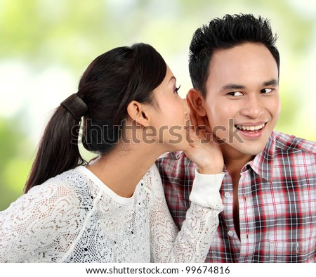 young woman whispering something to her boyfriend - stock photo