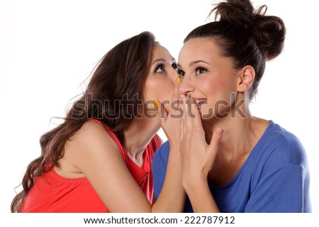 young woman whispers to her mate funny news - stock photo