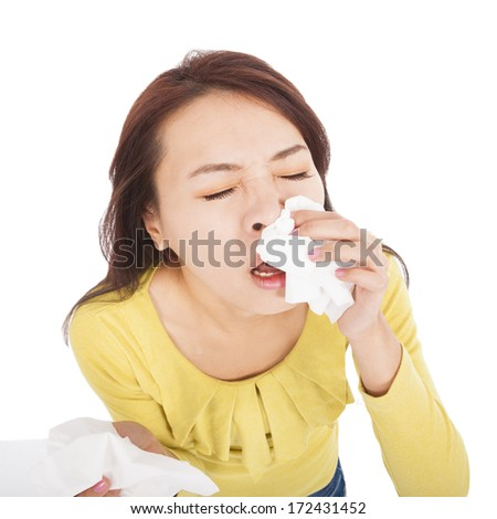 young woman with a an allergy sneezing into tissues - stock photo