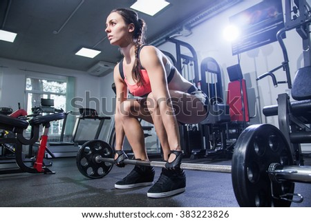 young woman with a barbell in the gym - stock photo
