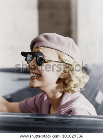 Young woman with a beret and sunglasses in a car, on the go - stock photo