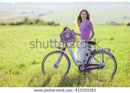 Young woman with a bicycle on green field on a sunny day - stock photo