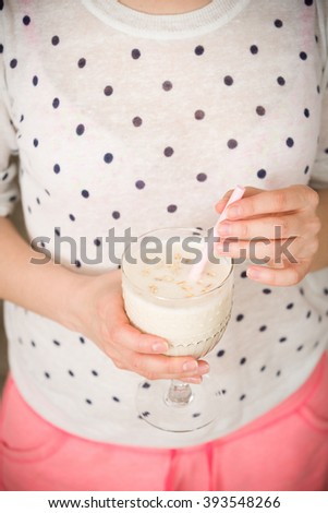 Young woman with a big glass of healthy smoothie served with a straw and oats. Hands holding milkshake. Stars background. Dairy snack or breakfast. - stock photo