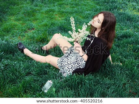 Young woman with a branch of a blossoming tree sitting on the grass , using smartphone to listening music with headphone - stock photo