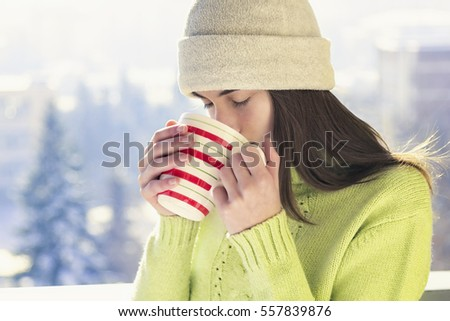 Young woman with a cup of hot drink on snowy winter walk in nature.