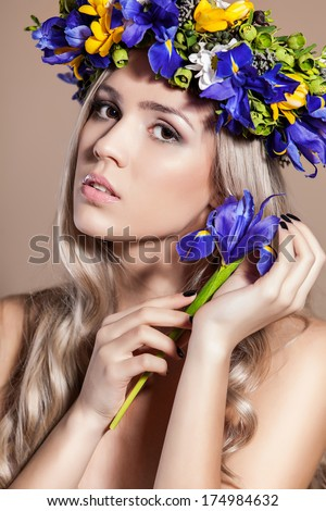 Young woman with a flower arrangement in her hair smiling at the camera - stock photo