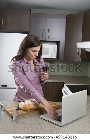 Young woman with a glass of wine and a house bread that has been cut, working on a laptop