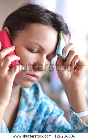young woman with a handkerchief and a cold call the doctor - stock photo
