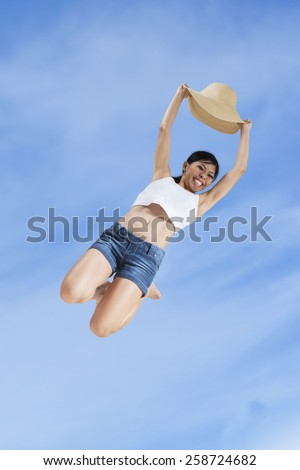 Young woman with a hat enjoy holiday and jump under blue sky - stock photo