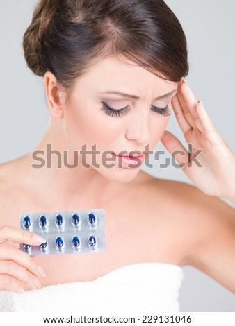 Young woman with a headache holding a pack of tablets for medication as she winces in pain and touches her forehead with her hand - stock photo