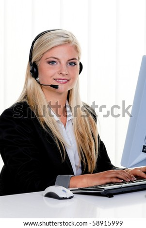 Young Woman with a headset and computer at Hotline.