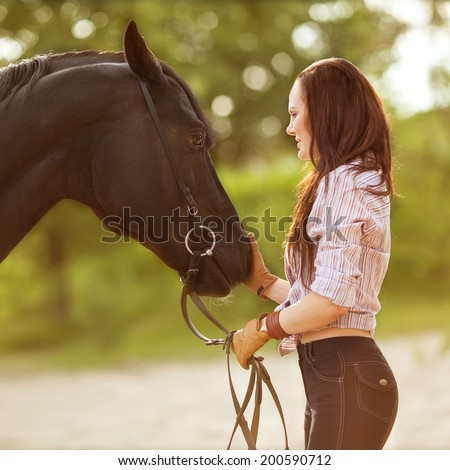 Young woman with a horse in park near the river - stock photo