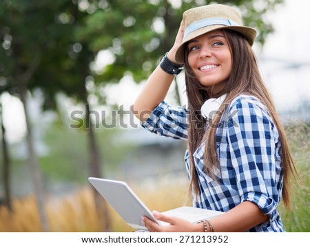 Young woman with a laptop outdoors - stock photo
