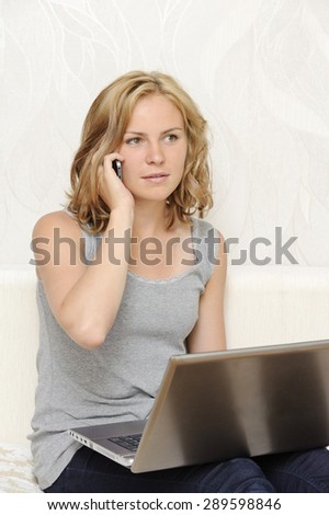 Young woman with a laptop talking on the phone - stock photo