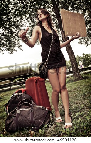 Young woman with a lot of luggage, trying to get a ride by hitchhiking. - stock photo