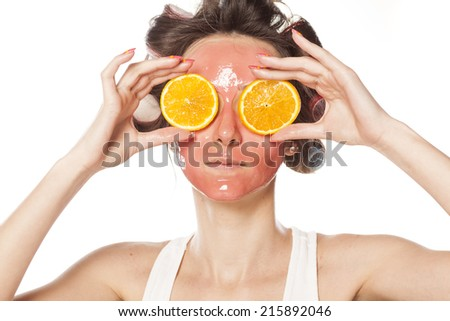 young woman with a mask and curlers holding a piece of orange on the eyes - stock photo