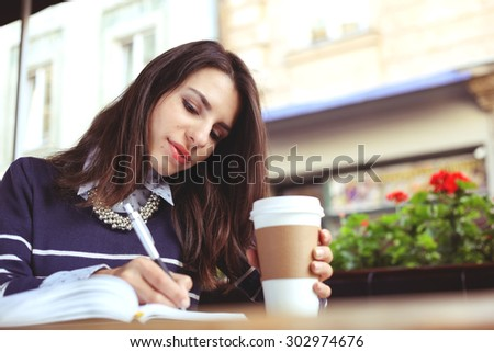 Young woman with a notebook and a paper cup of coffee. Write in a notebook. Working in the cafeteria. Summer patio. Business meeting. Business casual, business fashion.