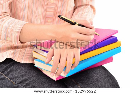 young woman with a pen and a stack of books, isolated on white background - stock photo
