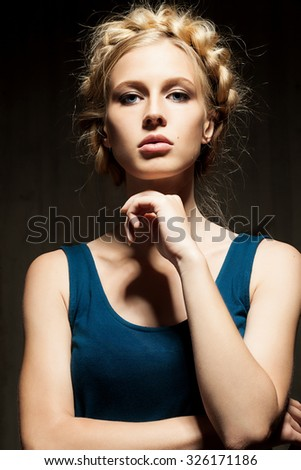 Young woman with a plait of blond hair on dark background - stock photo