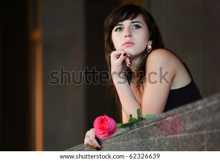 Young woman with a red rose.