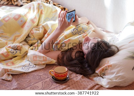 Young woman with a smartphone in the morning lying in bed . - stock photo