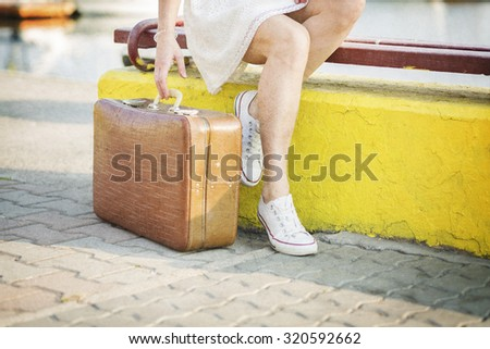 Young woman with a suitcase ready for a summer vacation - stock photo