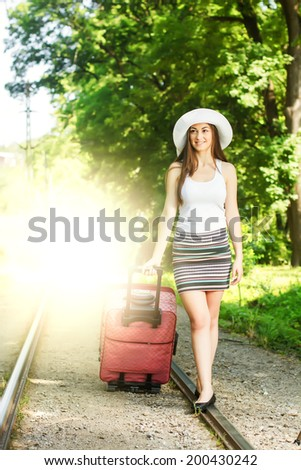 Young woman with a suitcase ready for travel.
