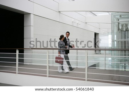 Young woman with a suitcase walking next to a young man on a gateway
