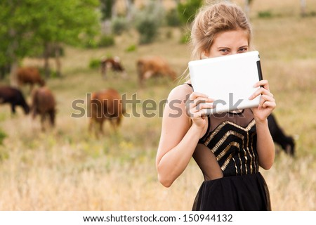 Young woman with a tablet pc in a countryside - stock photo