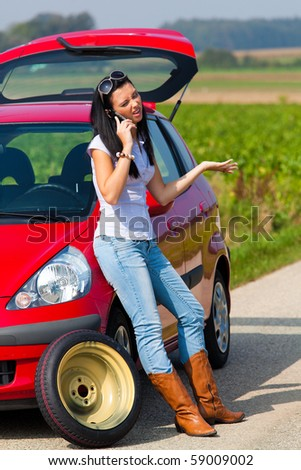 Young woman with a tire in a car breakdown - stock photo