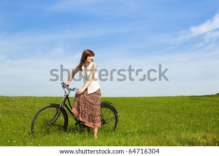 Young woman with a vintage bicycle on a green meadow - stock photo