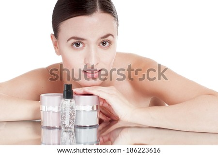 Young woman with  a well-groomed skin near the creams cosmetics. Skin care concept. - stock photo