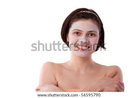Young woman with a white clay facial mask. Enjoying a day at the spa. Health & Beauty Concept: Facial and spa