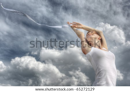 Young woman with a white ribbon and raised hands on clouds background - stock photo