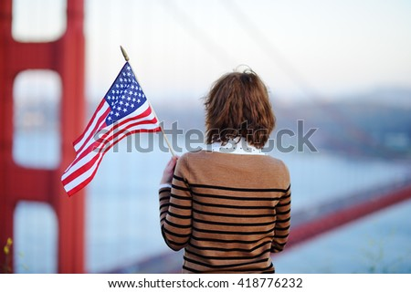 Young woman with american flag looking on famous Golden Gate bridge in San Francisco, California, USA