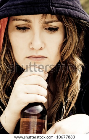 Young woman with an alcohol bottle in her hands - stock photo