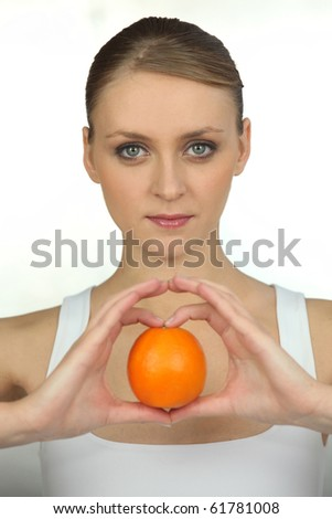 Young woman with an orange on white background