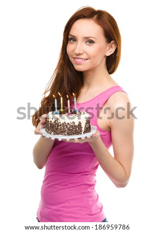 Young woman with anniversary cake, isolated over white - stock photo