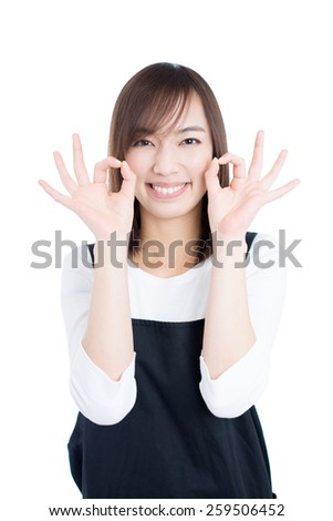 young woman with apron showing OK sign, isolated on white background