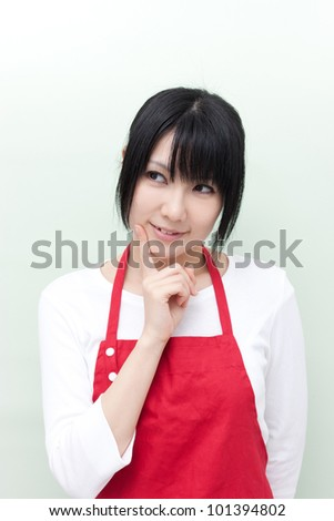 young woman with apron thinking - stock photo